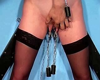 zware gewichten hangen met klemmen aan schaamlippen van sexslavin