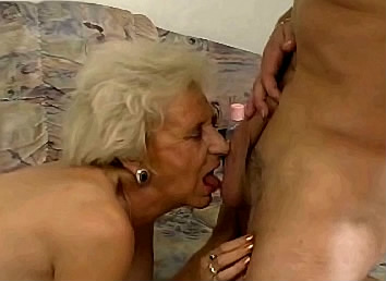 gerimpelde oma likt de lul en ballen van jongen